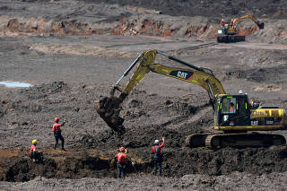 Members of a rescue team search for victims of a collapsed tailings dam owned by Brazilian mining company Vale SA, in Brumadinho