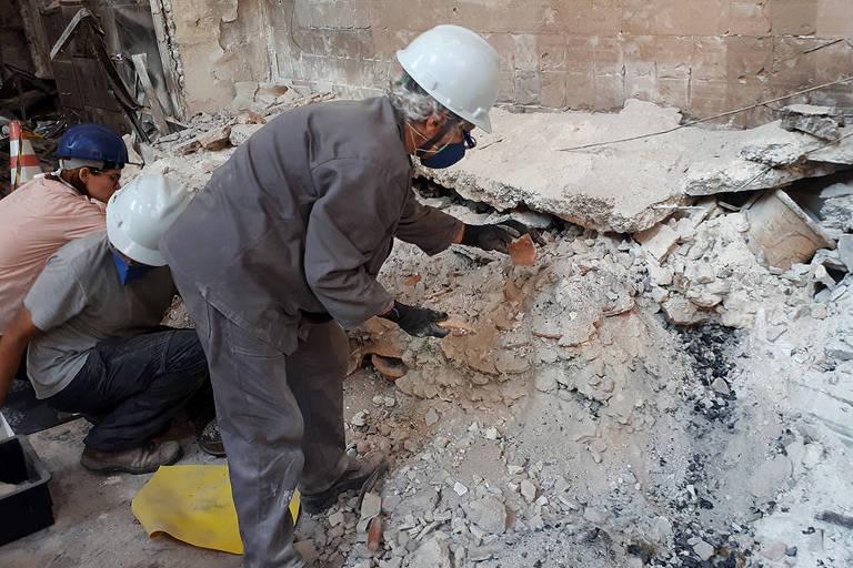 A arqueóloga Angela Rabello resgata fragmentos de cerâmica indígena em meio aos escombros do incêndio do Museu Nacional. À direita vê-se um vaso marajoara recuperado praticamente intacto no fim de janeiro