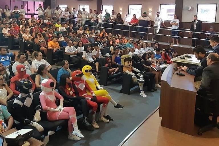 auditório lotado; membros da plateia estão fantasiados com os figurinos normalmente usados por funcionários de trenzinhos da alegria, como power rangers, personagens da turma da mônica e outros