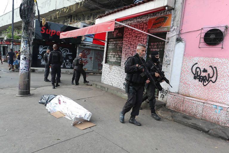 Policiais passam por corpo de homem na entrada de Jacarezinho, em operação feita após morte de PM