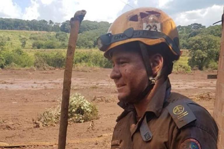 O cadete, sentado em meio à lama, vestindo uniforme de bombeiro e de capacete, todo sujo do barro que vazou da barragem de Brumadinho