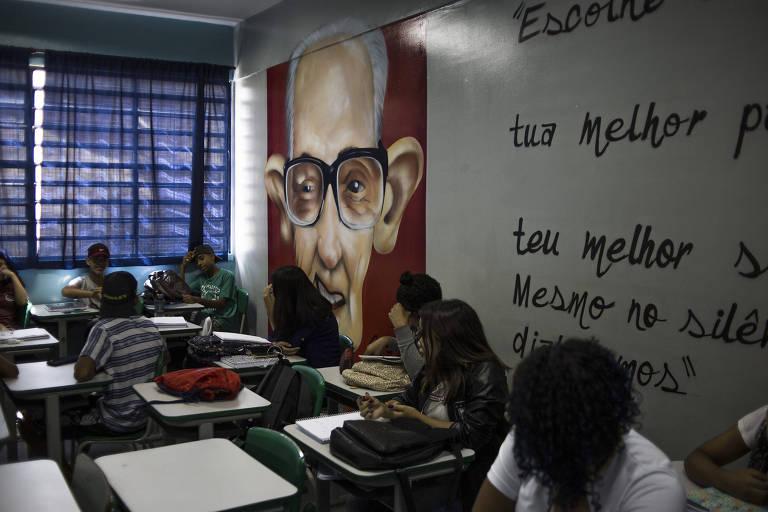 A pintura do poeta a Carlos Drummond de Andrade, que aparece sorridente, com grande óculos e pintado em um fundo vermelho; alunos estão sentados em suas carteiras prestando atenção à aula