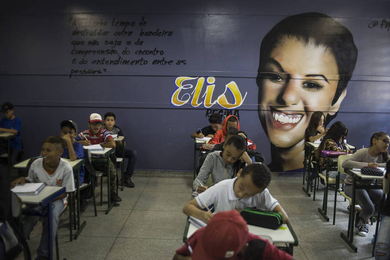 Desenho feito em grafite da cantora Elis Regina em foto no fundo da sala, à frente alunos sentados em suas carteiras escrevem