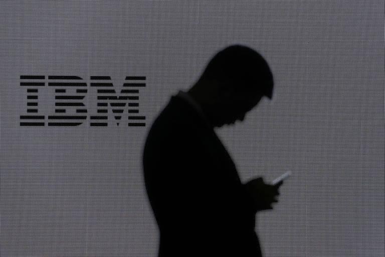 Homem olha para celular em frente ao logo da IBM