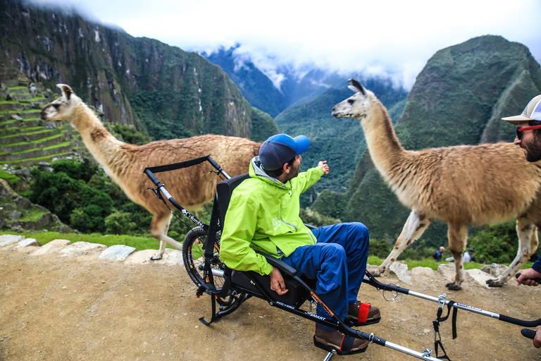 Homem em cadeira de rodas adaptada, com animais ao fundo