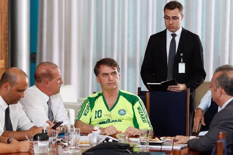 O presidente Jair Bolsonaro, vestido com camisa do Palmeiras, em reunião com ministros no Palácio da Alvorada