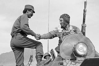 FILE PHOTO: A garlanded Russian soldier shakes hands with an Afghan soldier who climbed up on the tank to welcome more than 1,000 Soviet troops returning from the eastern city of Jalalabad