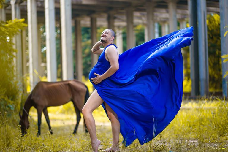 Bruno, que usa um vestido azul esvoaçante, está em um campo fazendo pose de grávida: uma mão na barriga e outra atrás da cabeça. Ao fundo, um cavalo pasta.