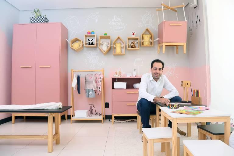 Homem de camisa branca sentado em mesa pequena, em ambiente com móveis cor de rosa