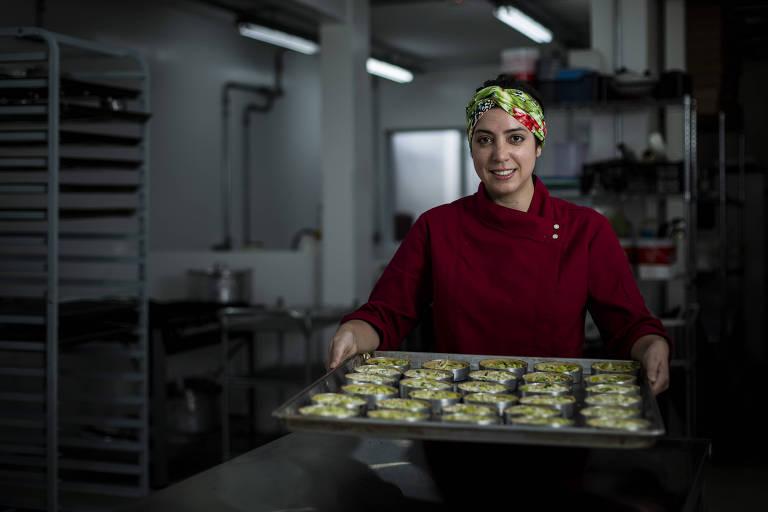 Mulher com blusa vermelha segura bandeja com tortas