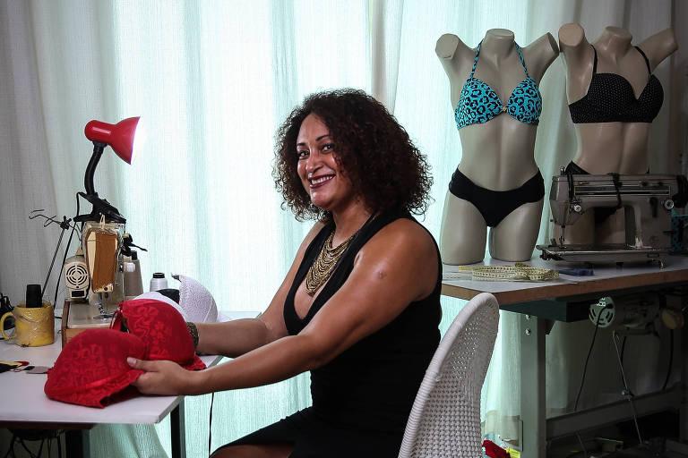 Mulher sentada em frente a uma mesa na qual há uma máquina de costura