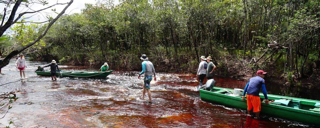 Turistas empurram canoa no igarapé Daracuá, que dá nome à comunidade local
