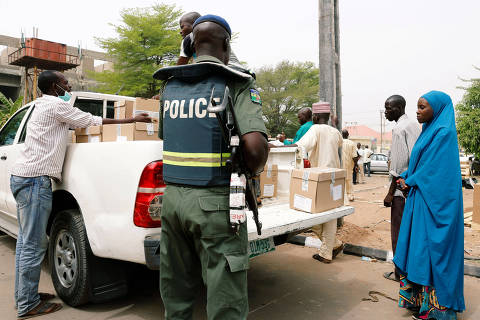 A police member oversees Ad-hoc staff loading boxes onto a truck during the distribution of election materials at the INEC office in Yola, in Adamawa State, Nigeria February 15, 2019. REUTERS/Nyancho NwaNri ORG XMIT: GGG-NGA46