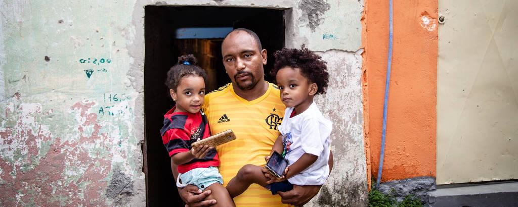 Cristiano Esmerio, pai do goleiro Christian, uma das vítimas, segura os gêmeos Lavinea e Leandro