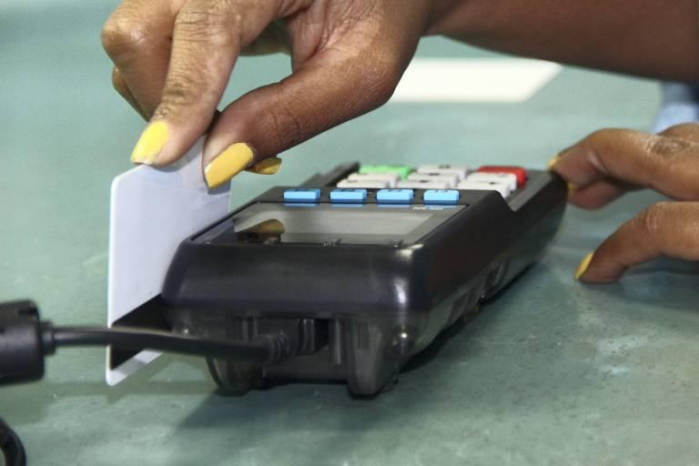Mão passa cartão de pagamento em máquina