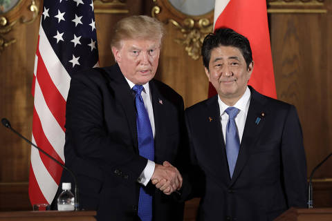 TOPSHOT - US President Donald Trump shakes hands with Japan's Prime Minister Shinzo Abe (R) during a news conference at Akasaka Palace in Tokyo on November 6, 2017. / AFP PHOTO / POOL / Kiyoshi Ota