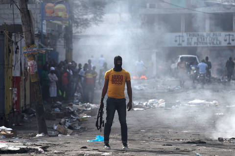 A man holds a weapon next to burning barricades during anti-government protests in Port-au-Prince, Haiti, February 17, 2019. REUTERS/Ivan Alvarado ORG XMIT: GGGIA109
