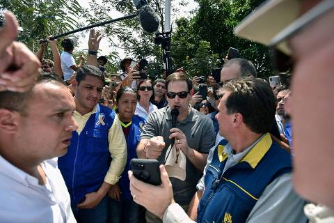 US senator Marco Rubio (C) speaks on a video call with Venezuelan opposition leader and self declared acting president Juan Guaido, at the Simon Bolivar international bridge in Cucuta, Colombia, border with San Antonio de Tachira, Venezuela on February 17, 2019,  where he arrived to assess the situation after humanitarian aid shipments sent by the US government for Venezuela were stockpiled at a collection center in the Colombian border. - Thousands of volunteers in Venezuela will begin mobilizing on Sunday to bring American aid into their crisis-hit country despite a blockade by President Nicolas Maduro who claims the assistance could be cover for a US invasion. US aid that has been piling up in the Colombian border town of Cucuta has become the frontline of the confrontation between Guaido and Maduro. (Photo by Luis ROBAYO / AFP)