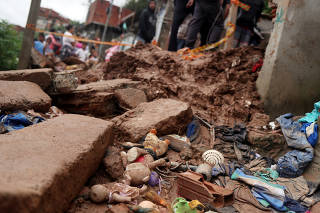 Residents look at a house damaged in a mudslide after heavy rains in Maua