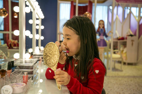 A young girl applies lipstick made for children at PriPara Kids Cafe in Yongin, South Korea. MUST CREDIT: Photo for The Washington Post by Jean Chung