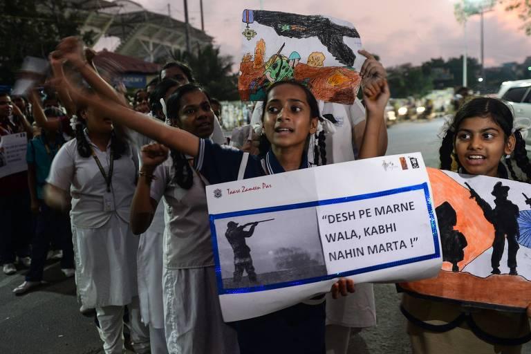Estudantes indianos exibem cartazes e protestam contra o Paquistão durante procissão em homenagem aos mortos do atentado na Caxemira indiana