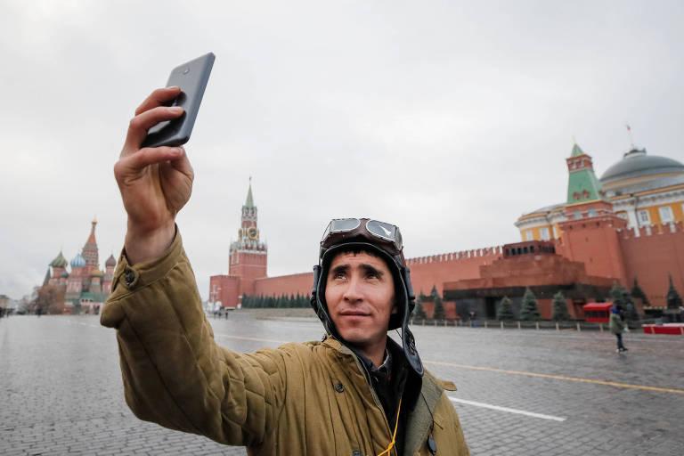 Soldado russo, em uniforme histórico, tira selfie em frente ao mausoléu de Lênin e ao Kremlin, em Moscou