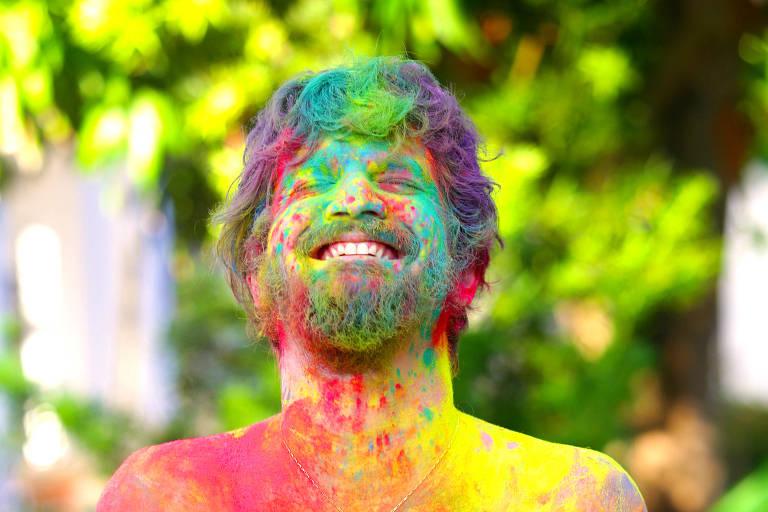 Saulo Fernandes coberto de pó colorido; ele levará tradição de festival sagrado indiano para um de seus dias de trio no Carnaval de Salvador