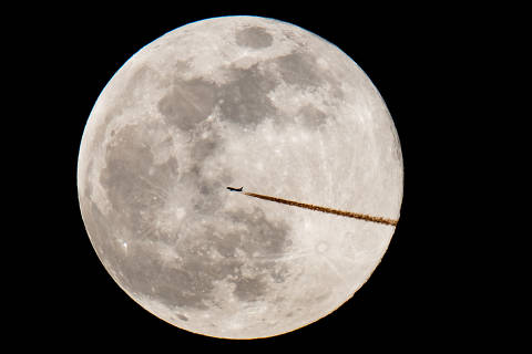 A plane flies past the full moon in Nuremberg, on February 19, 2019. (Photo by Daniel Karmann / dpa / AFP) / Germany OUT ORG XMIT: 90-030429