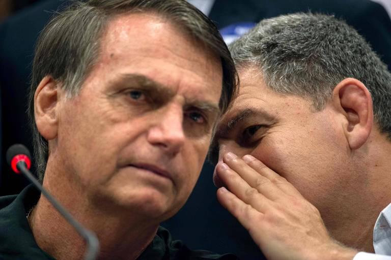 À direita, Bebianno fala próximo ao ouvido direito de bolsonaro, usa a mão para tapar a boca. À esquerda, o presidente Jair Bolsonaro escuta enquanto olha para a frente