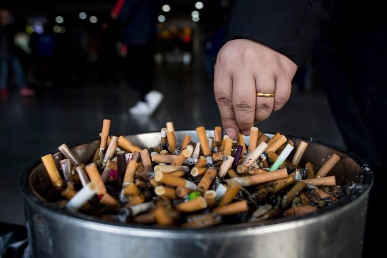 Pessoa apaga um cigarro em recipiente cheio de bitucas