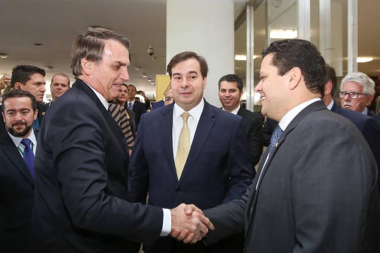 Presidente da República, Jair Bolsonaro, cumprimenta o presidente do senado, Davi Alcolumbre, antes da entrega da proposta de forma da Previdência; Rodrigo Maia aparece no centro da imagem fazendo uma careta