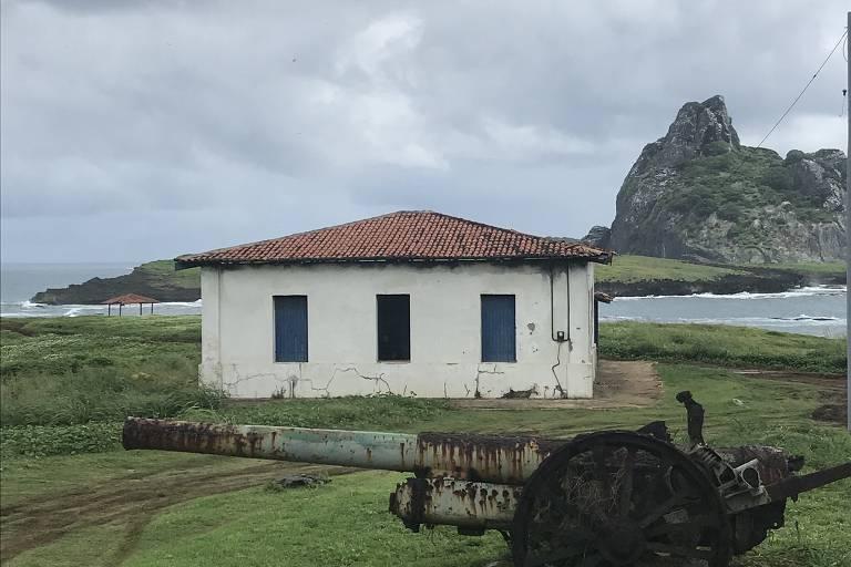 Canhão antigo e casa simples em gramado, com mar e morro ao fundo