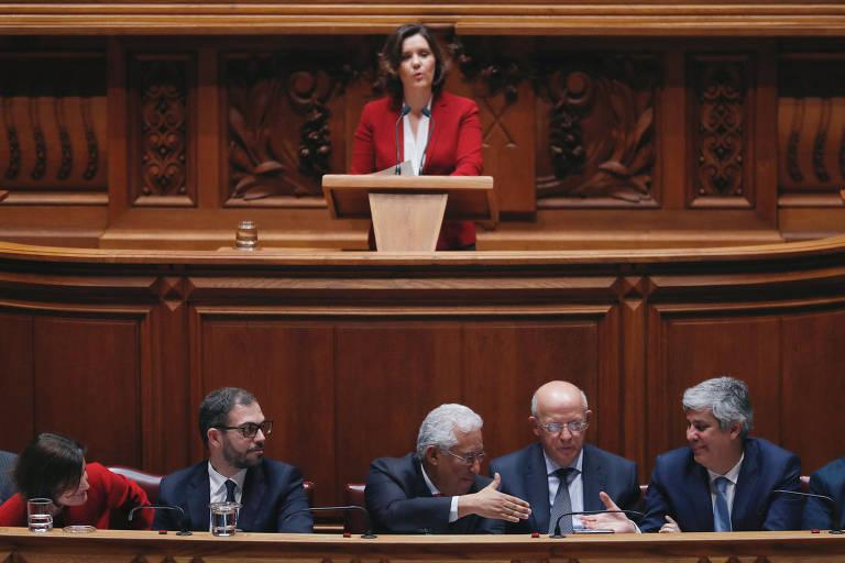 Líder do partido CDS-PP, Assunção Cristas, discursa enquanto primeiro-ministro de Portugal, António Costa, cumprimenta o ministro da Fazenda, Mario Centeno, durante debate sobre moção de censura no Parlamento
