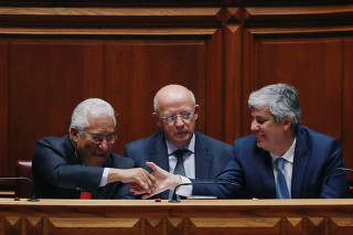 Portugal's Prime Minister Antonio Costa shakes hands with Finance Minister Mario Centeno during the debate of a motion of censure at the parliament in Lisbon