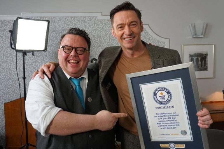 Craig Glenday, editor-chefe do Guinness, entrega certificado do livro dos recordes ao ator Hugh Jackman