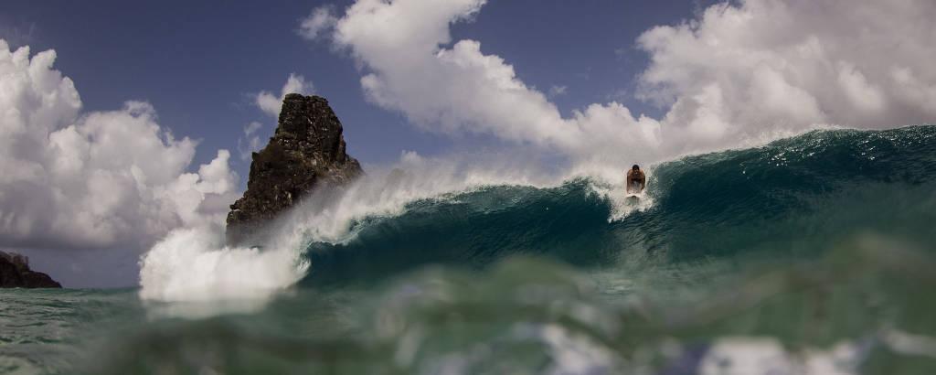 Surfista em onda, com morro ao fundo