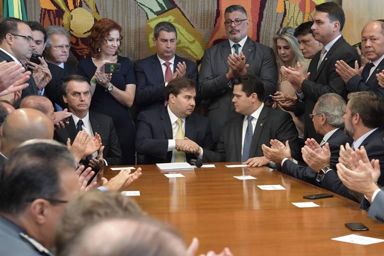 O presidente da Câmara, Rodrigo Maia (centro), aperta a mão do presidente do Senado, Davi Alcolumbre, durante entrega da PEC da reforma da Previdência por Jair Bolsonaro