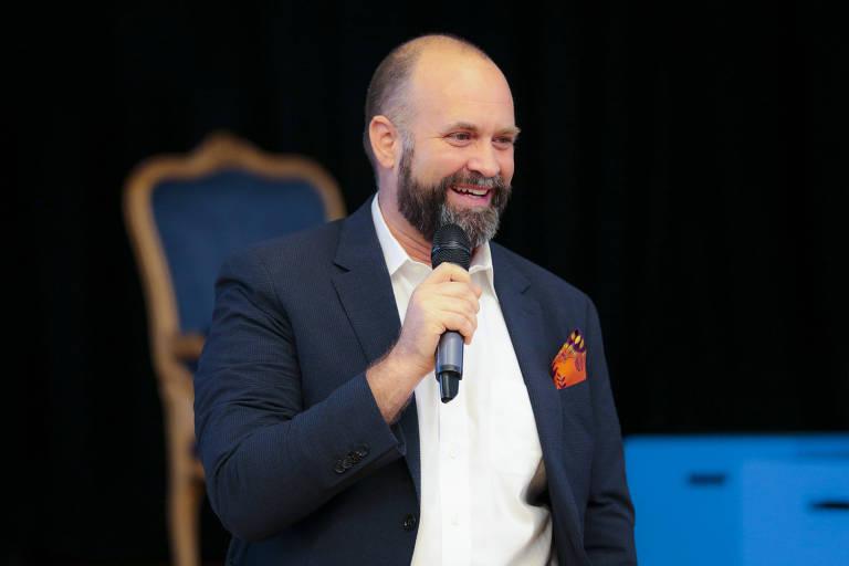 O professor, um homem branco e careca, de barba, vestido de blazer azul e camisa branca, fala ao microfone em uma palestra