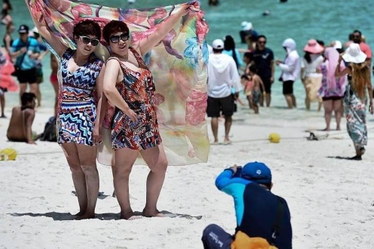 Pessoas fazem pose para foto em praia cheia