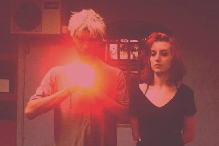Dois atores apontam lanterna vermelha para o espelho