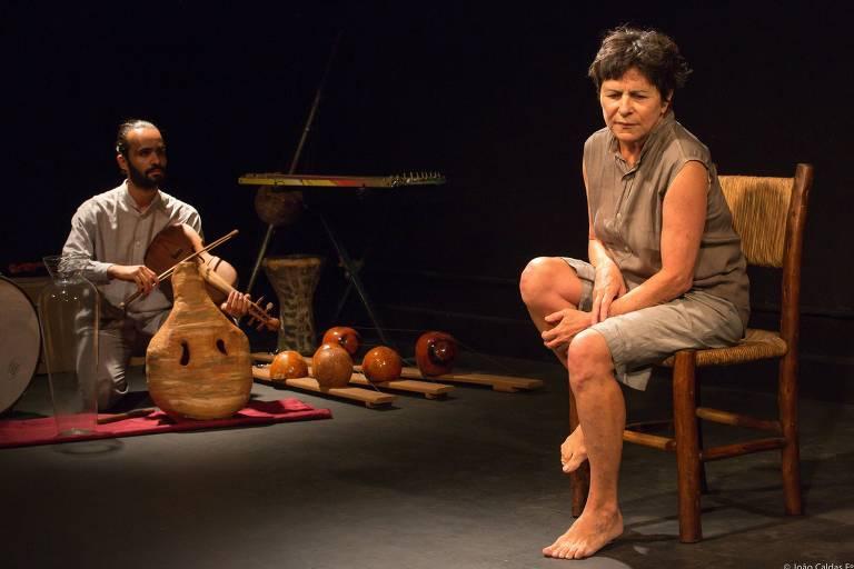 Uma mulher aflita se senta em uma cadeira; um músico toca violino agachado ao seu lado
