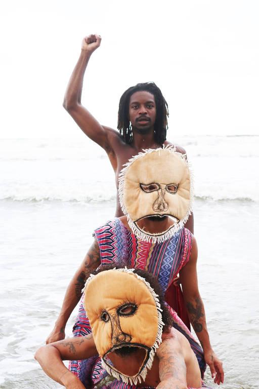Homem negro branda a mão no ar; duas pessoas usando máscara enfileiram-se a sua frente