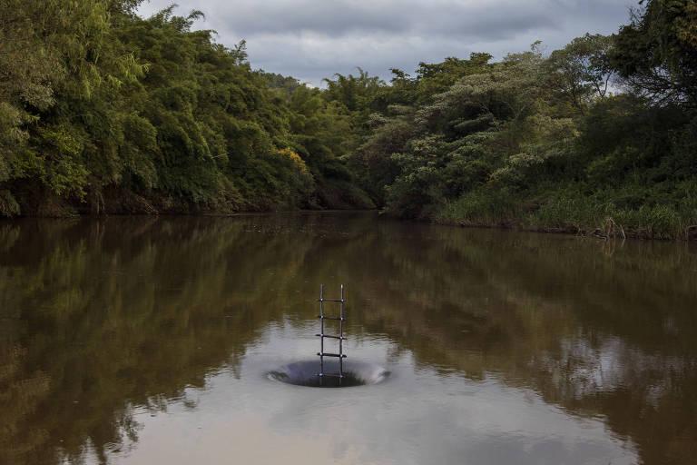 Em um rio, uma escada de madeira parece ser sugada por um redemoinho