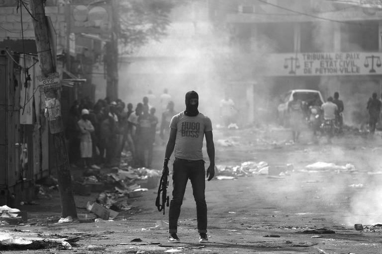 Homem segura arma durante protestos contra o governo em Porto Príncipe, no Haiti