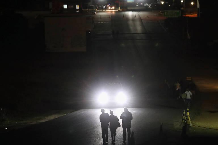 De noite, três pessoas andam em uma estrada; ao fundo, farol de carro mostra a silhueta das três pessoas; Fronteira entre Venezuela e Brasil em Pacaraima, Roraima, foi fechada na noite de quarta-feira (21)