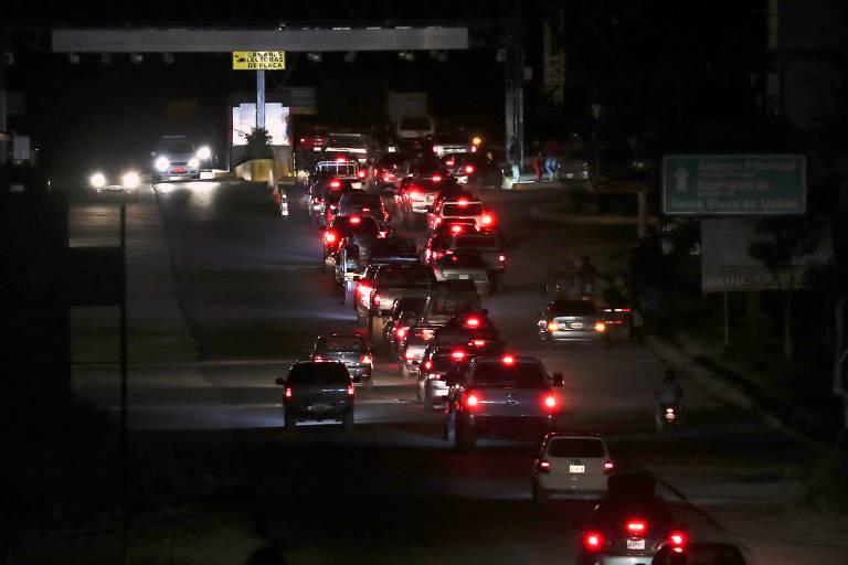Fila de carros espera para cruzar fronteira em Pacaraima, na quinta (21) à noite, antes do fechamento da passagem