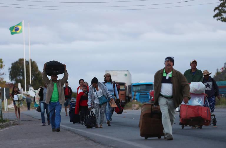 Pessoas caminham após cruzar fronteira com a Venezuela e Brasil em Pacaraima, Roraima, na manhã de sexta (22)