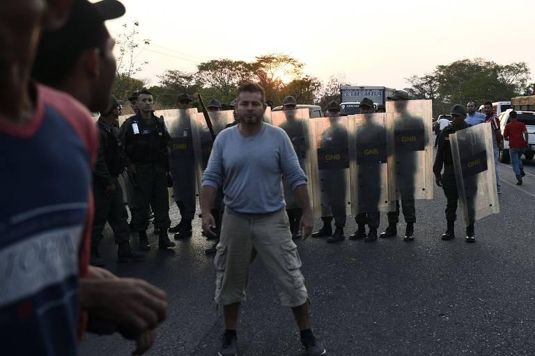 Moradores venezuelanos ficam irritados quando a Guarda Nacional bloqueia a rodovia principal para impedir que os comboios cheguem à fronteira com a Colômbia