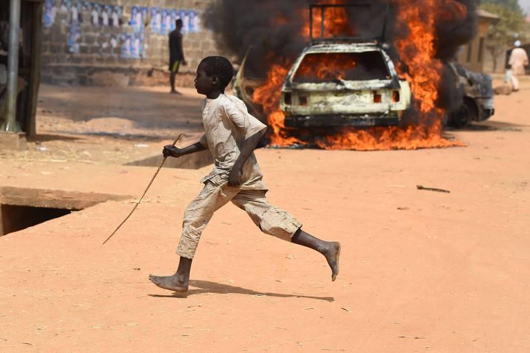 Menino corre em local onde carros foram incendiados durante confronto entre apoiadores dos dois partidos que lideram a eleição na Nigéria