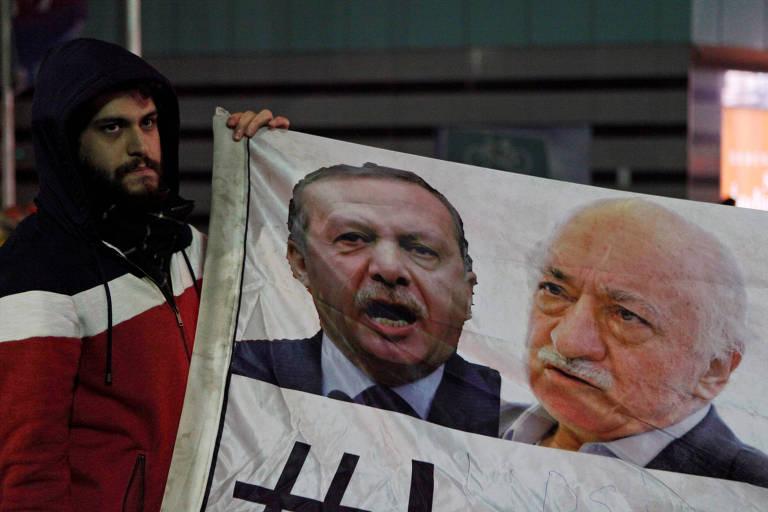 Um manifestante segura fotos do primeiro-ministro turco Tayyip Erdogan (E) e do clérigo turco Fethullah Gülen (D)